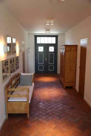 Sitzbank, Schrank und Bilder im Eingangsbereich