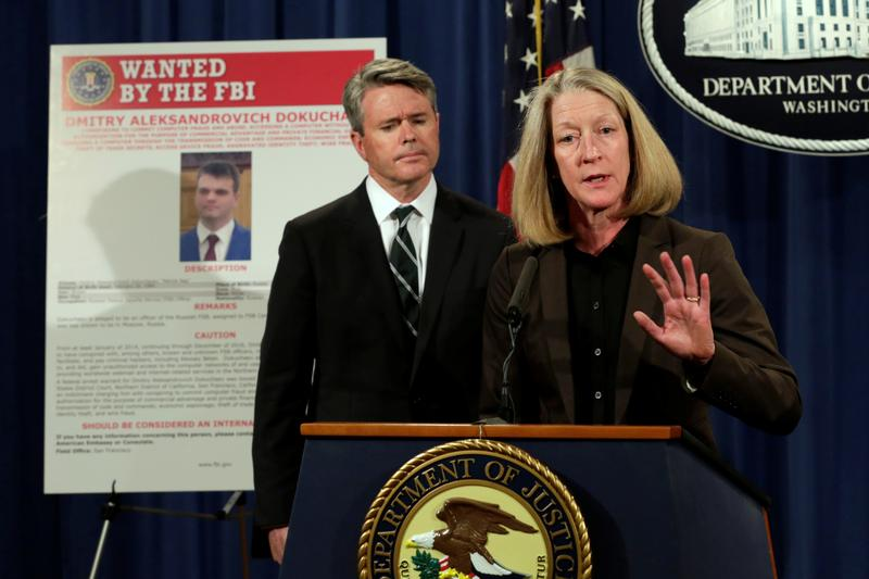 Acting AAG for National Security McCord speaks in front of a poster of a suspected Russian hacker at the Justice Department in Washington