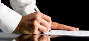 Close-up of the hands of a man wearing white shirt while signing with a pen an official paper document or agreement placed on a black reflective table with copy space on black background. ** Note: Shallow depth of field