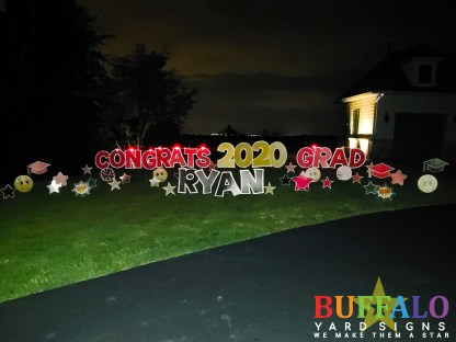 Red congrats grad yard sign for graduations with stars, smiley faces, and graduation caps