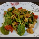 Tofu and pasta dish with spinach, red and green peppers, green olives, pineapple, and peas.