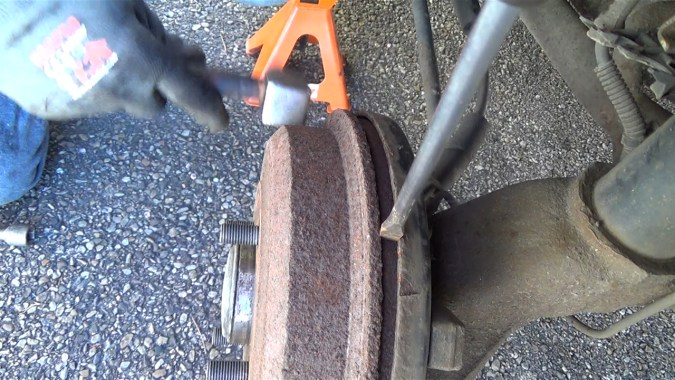 Taper avec un marteau rivoir sur le côté du tambour tout en faisant levier avec un tournevis