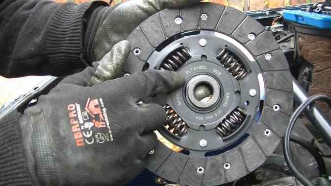 """Le côté plat du disque d'embrayage marqué """"FLY WHEEL"""" (volant moteur) doit être positionné  côté moteur"""