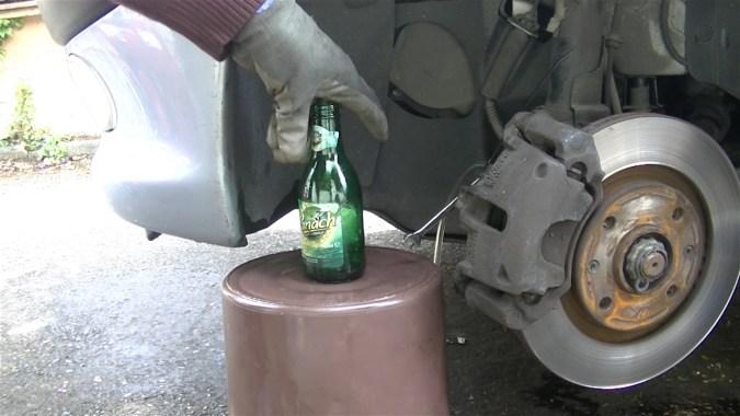 Placer une bouteille de 25 cl à la hauteur de la vis de purge