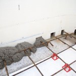 Concrete being poured through pre-cut holes at the bottom of the wall