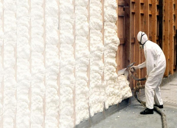 Trained applicator applying spray polyurethane foam insulation in wall cavities.
