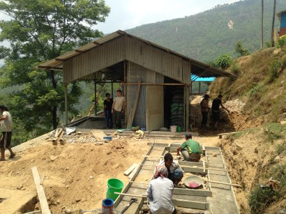 Masons working on the toilet building, laying out formwork and rebar for the structure.