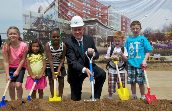 Hospital President and CEO Bill Considine gets ready to shovel the ceremonial dirt with several kids.