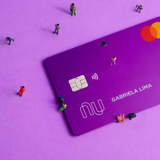 Little toy figures around Nubank's purple credit card