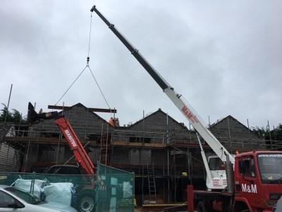 Crane lifting ridge beams into place