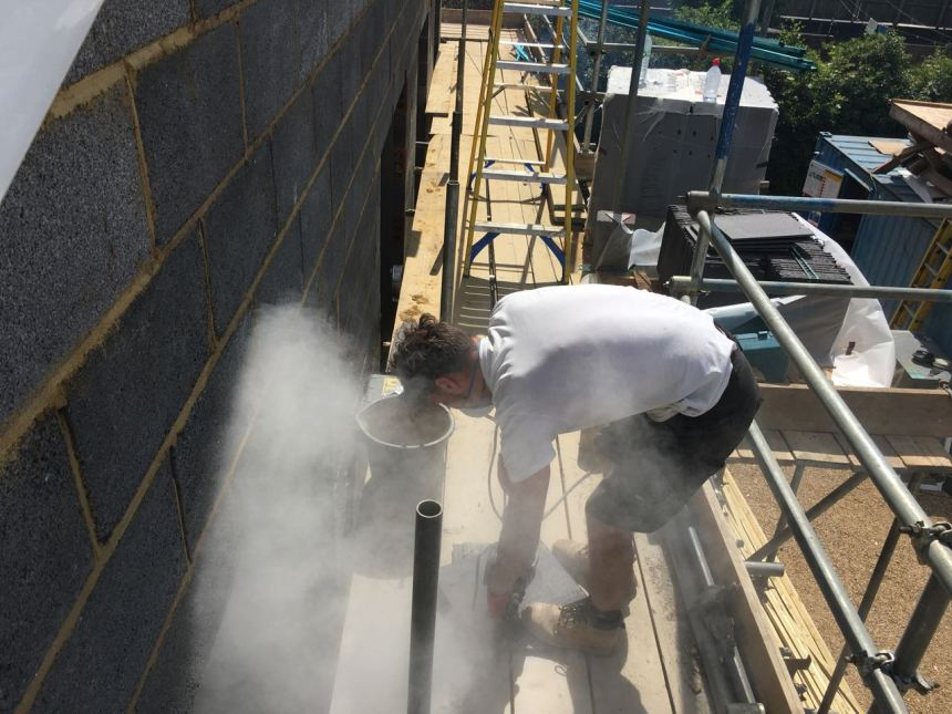 Roofer cutting tiles