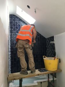 Bathroom deep blue Metro tiles being fitted