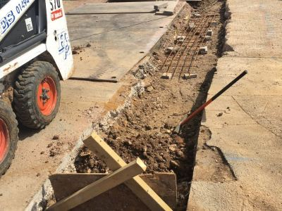 Utility service trench backfilled with concrete reinforced with steel rebar