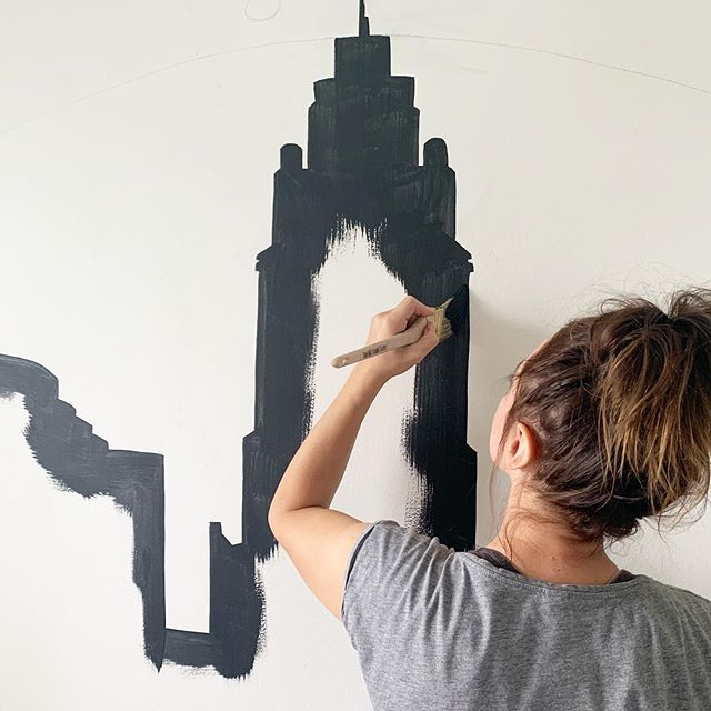 Sarah from Nestrs paints the Columbus skyline on the wall to create an experience for her guests.