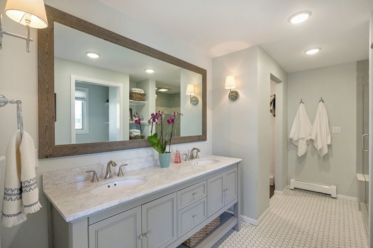 This bathroom is staged with crisp white towels, a bright plant and decluttered counters.