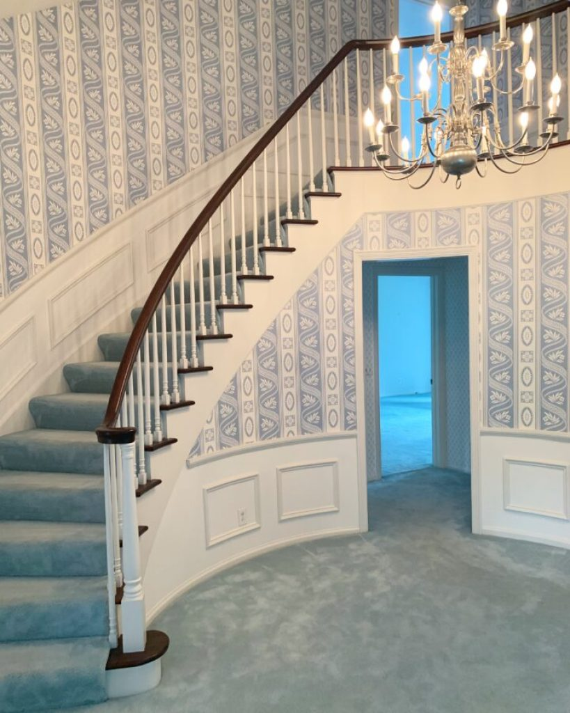 The beautiful foyer of our new home with the blue carpet and wallpaper.