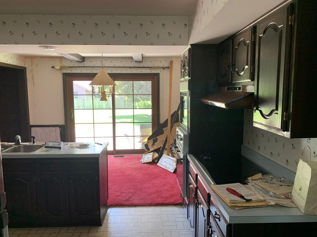 The eating area in the kitchen with red carpet and wallpaper