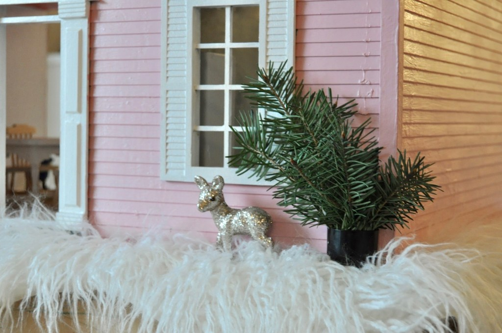 Faux plant & glitter deer outside the pink house