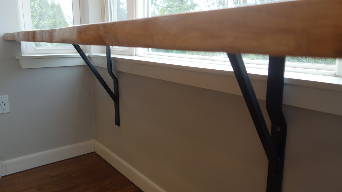 blackened steel braces for floating slab table