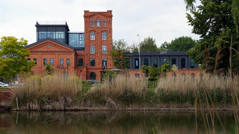 Budynek główny SSE w Łodzi widziany z perspektywy stawu