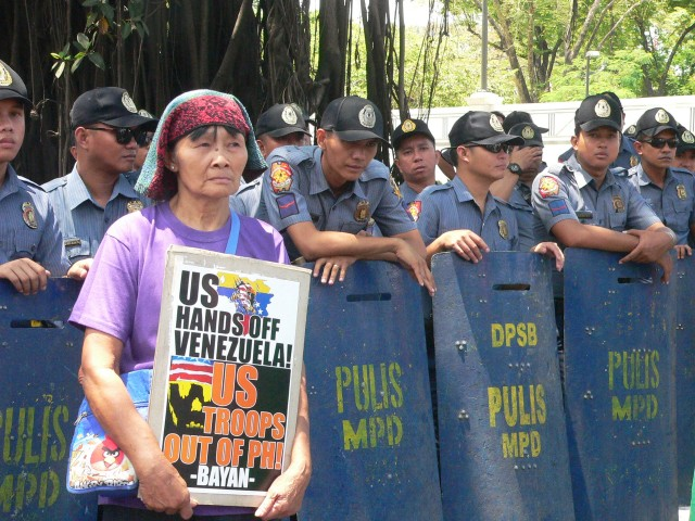 Woman protester in front of anti-riot police at the US embassy. (Photo by D.Ayroso/Bulatlat.com)
