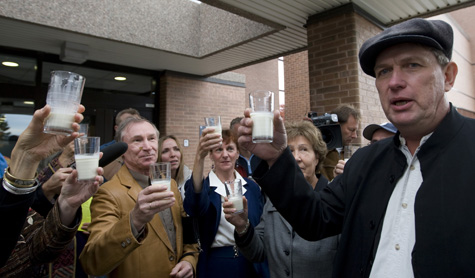 Schmidt (right), is surrounded by supporters as he toasts to the queen with a glass or 'Raw Milk' at a courthouse in Newmarket, Ontario