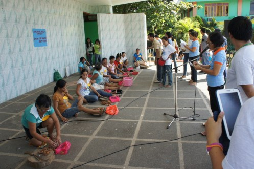 Staff from LGU Bulusan observe the contestants during the pili deshelling competition. (Bulusan, 2013).
