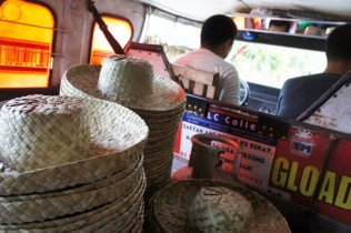 Karagumoy hats occupy the aisle. These are bound for hat traders in the Poblacion at 6 -7 pesos each.