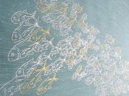 A school of gold and silver fish, hand-foiled onto bookcloth by The Bumblebee Bindery
