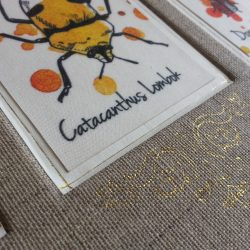 A partial closeup of a book bound in rough linen buckram, with an inset beetle image and gold foil details.