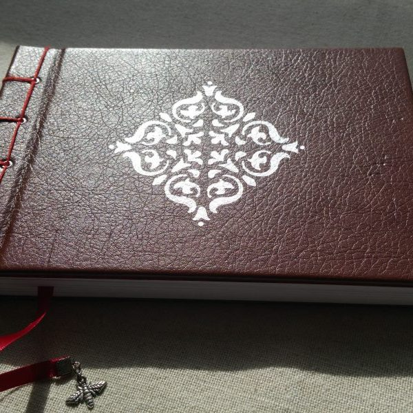 A brown notebook with red detailing and a silver flourish motif on the front cover