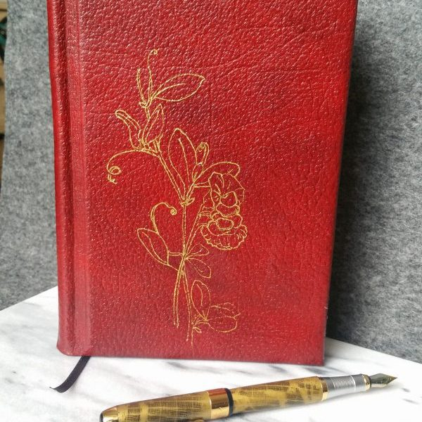 A red leather book with a golden illustration of sweet peas