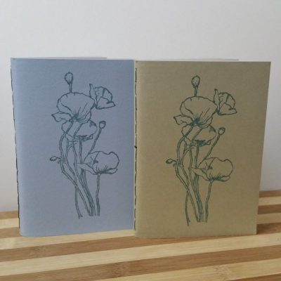 A pale blue, and a sandy beige, pocket book; each with a group of poppies stamped on the cover in metallic teal.