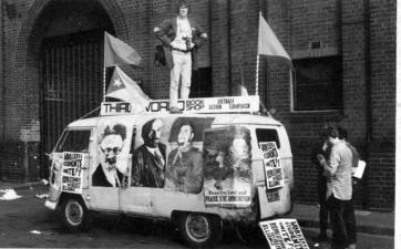 Preparing for May Day. Blue Fisher on top of decked-out kombi, Keith James at side.