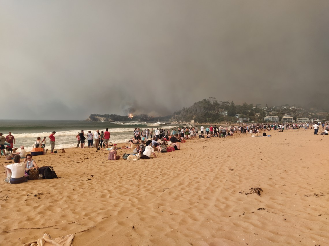 People on beach with fire in distance