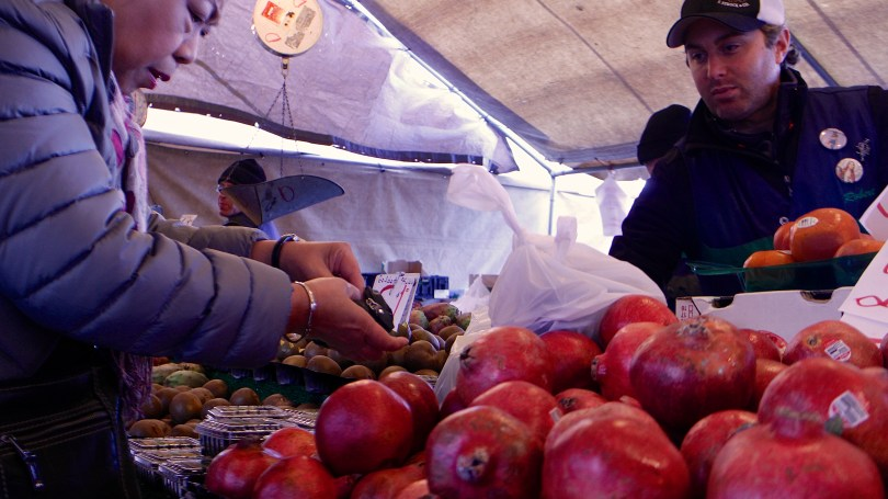 Haymarket vendor Salvatore Manella, right, helps a customer. Photo by Rebecca Jahnke.
