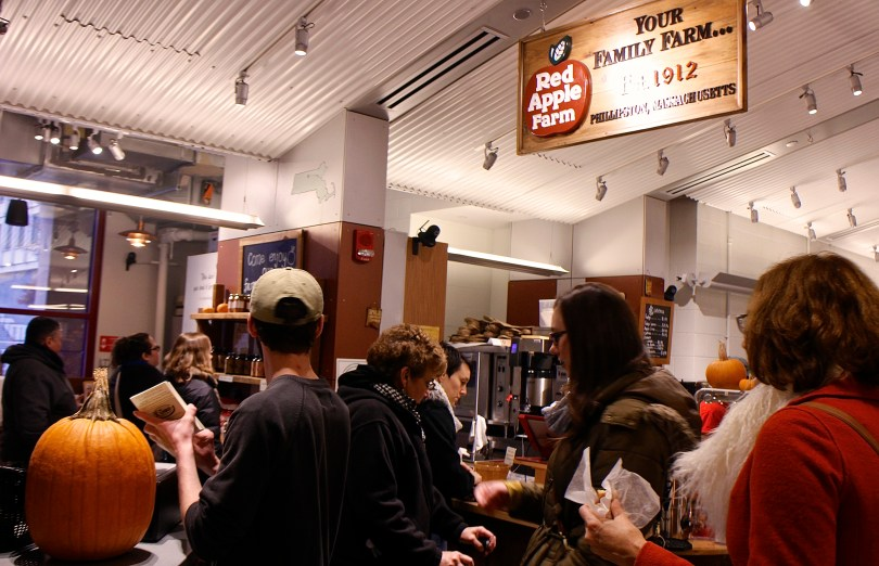 Crowds enjoying homemade cider donuts linger around the Public Market's Red Apple Farm stall. Photo by Rebecca Jahnke.