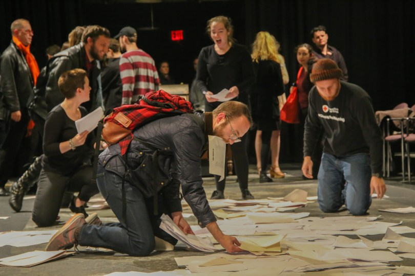 After the opera, attendees collect paper strewn on the stage during the performance. Photo by Silvia Mazzocchin/BU News Service