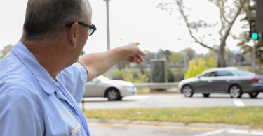 U.S. Postal Service worker Ron French points at the Harvard athletic complex that is in Allston just across the Charles River from where he stands adjacent to 986 Memorial Drive in Cambridge on Oct. 5, 2017. The Harvard property is now home to the annual Boston Calling music festival which Cambridge residents claim shook homes and rattled windows throughout the Memorial Day weekend last May. Photo: Gaelen Morse/BU News Service