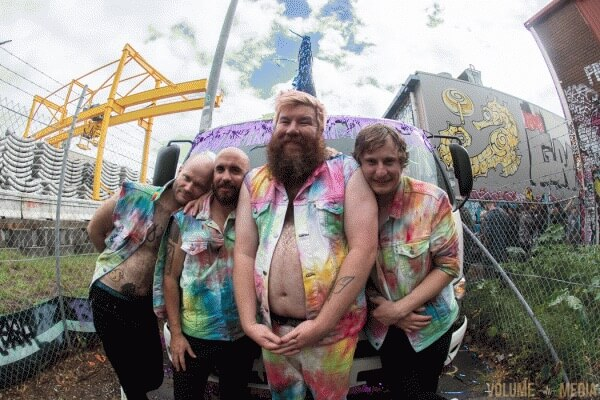 Photo of all band members outside wearing jackets covered in paint