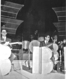 A snapshot of the Berigan band in action at an outdoor concert, summer 1938. L-R: Bassist Hank Wayland; guitarist/vocalist Dick Wharton; drummer Buddy Rich; tenor saxophonist Georgie Auld; trumpeter Irving Goodman.
