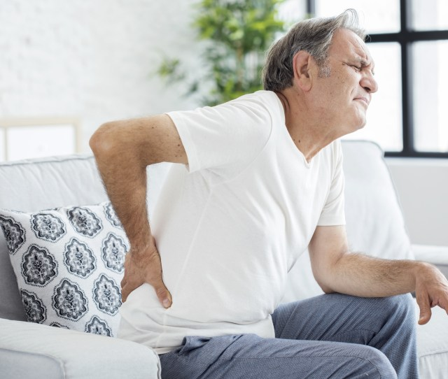 A Person Experiencing Sharp Lower Back Pain Symptoms
