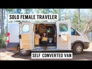 """An image of a woman sitting at a computer in her van home, with the title """"Solo Female Traveller, Self-Converted Van"""""""