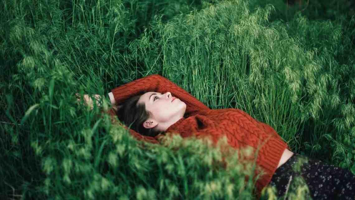 thoughtful woman lying on grass