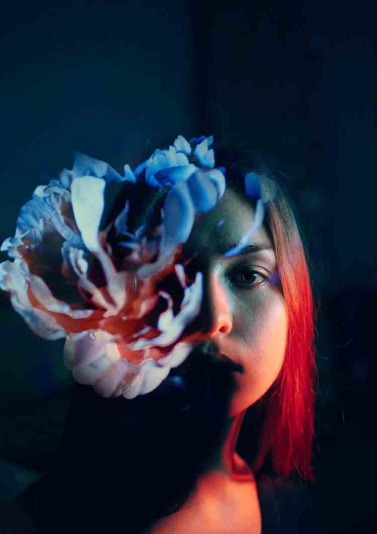 calm young woman with flower in dark room