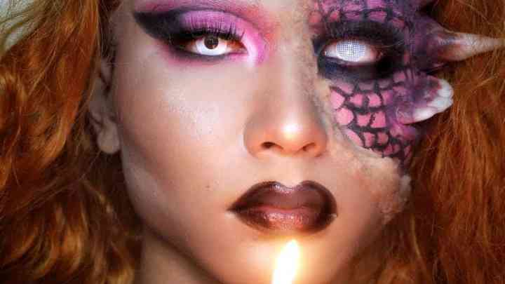 person with creepy makeup and burning candle