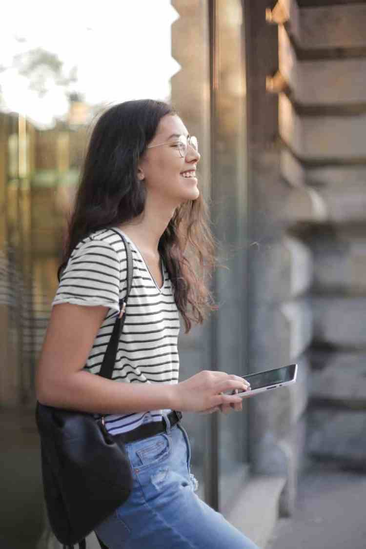 cheerful young woman using smartphone in street