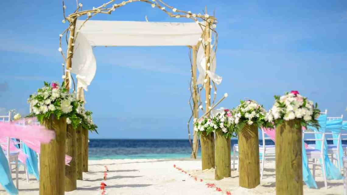 line of white flowers topped brown wooden pillars