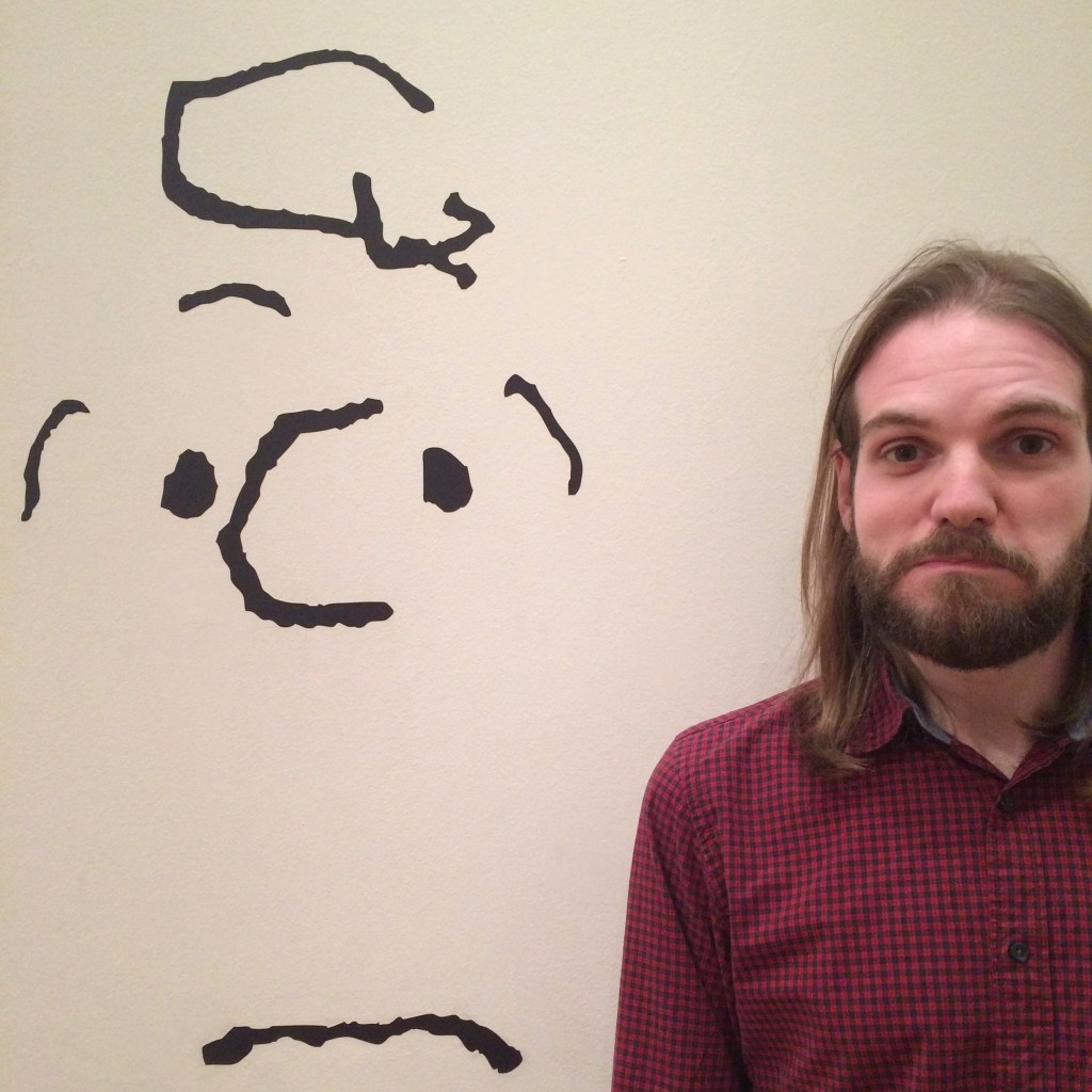 A picture of a man with long hair, wearing a burgundy shirt, standing in front of a minimal, impressionist mural of a character from Peanuts.