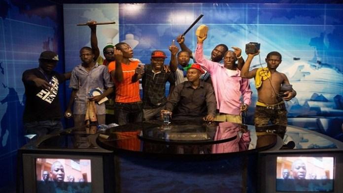 Hermann Bado parmi les insurgés à la Télévision nationale du Burkina le 30 octobre 2014 : il est assis avec le chapeau aux couleurs nationales